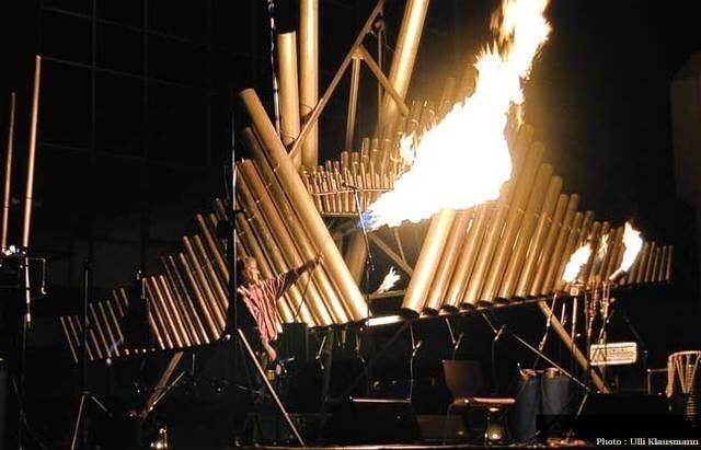 Photographie un homme tient une bruleur lançant une grande flamme devant des rangées de tube verticaux inclinés