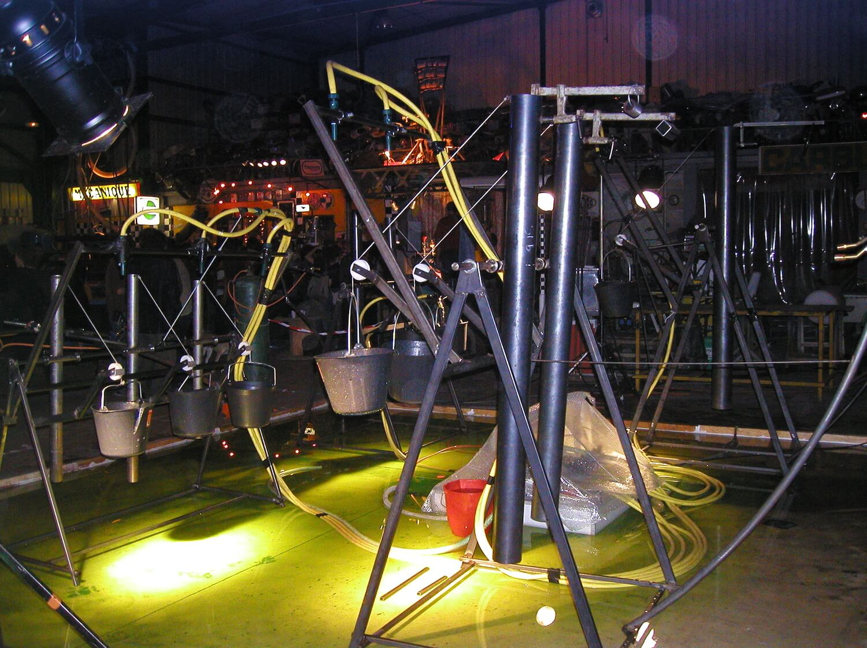 Photographie : bassin rempli de liquide jaune-vert fluorescent avec des installions de tubes et de seaux