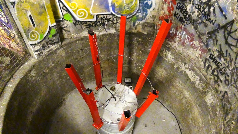Photographie dans le fond d'une cuve en ciment avec graffitis un fût de 200 litres blanc sert de support a 7 tubes rouges verticaux