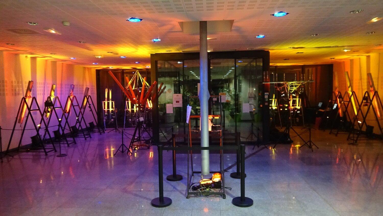 Photographie de tuyaux disposés sur les coté d'une salle éclairée en orange avec un grand tube gris au centre
