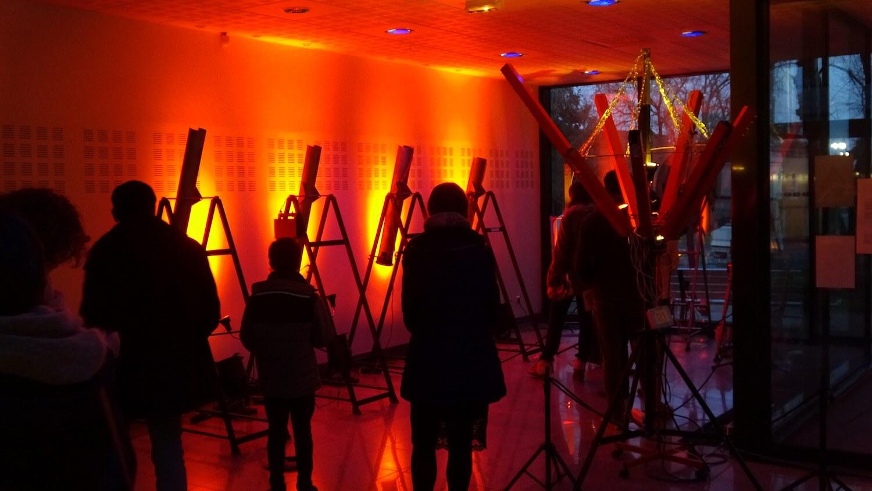 Public devant des tuyaux lumineux sur fond rouge orange