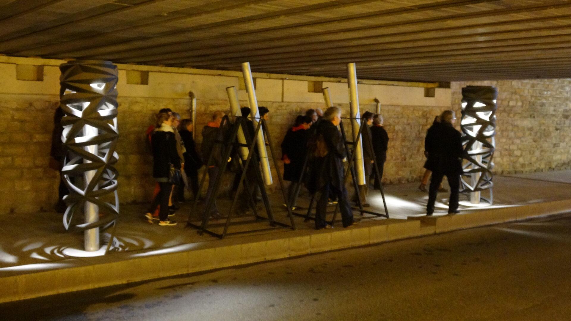 Photographie public circulant sur un trottoir d'une rue souterraine entre des lamapaires entourant des tubes gris sur support