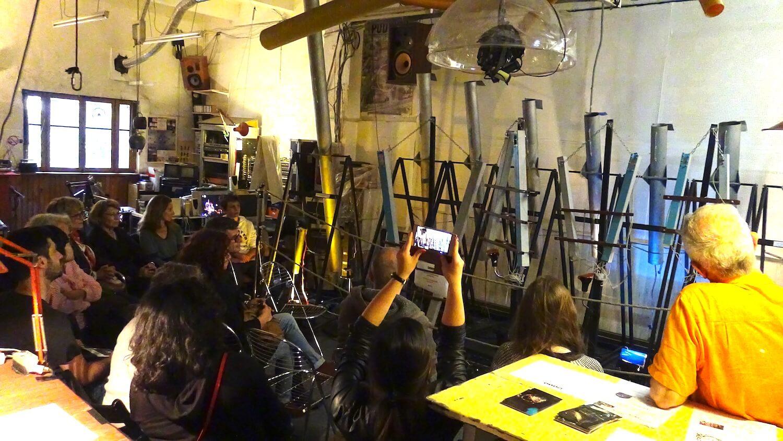 Photographie : public assis regardant une vingtaine de tubes gris verticaux dans une grande pièce