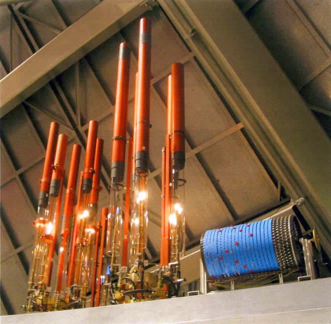 Photographie d'une quinzaine de tubes verticaux avec tubes en verre à leur base et flammes et sur le coté droit un cylindre à picot bleu de la partition