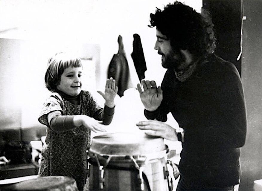 Photographie Noir et Blanc, une enfant tape sur une grande percussion avec concentration, accompagnée par Jacques Rémus