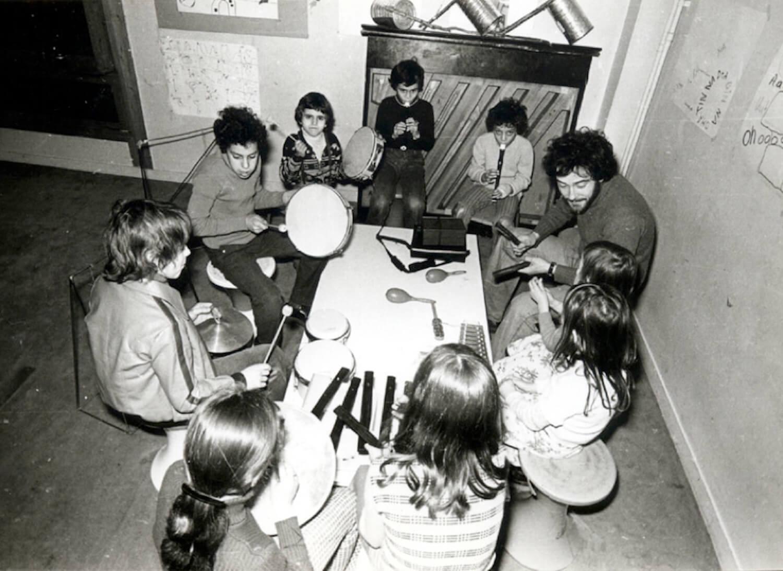 Photographie Noir et Blanc, autour d'une table basse , 9 enfants jouent de divers instruments de musique sous la direction de Jacques Rémus