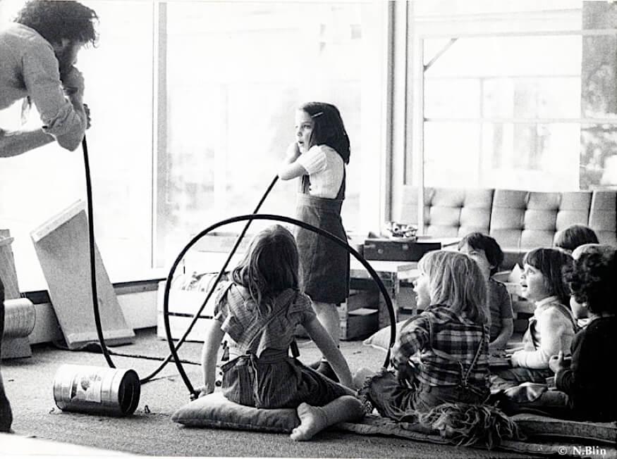 Photographie Noir et Blanc : jeune homme chante dans long tuyau au bout duqel une enfant écoute alors qu'un groupe d'enfants assis suit ce qui se passe