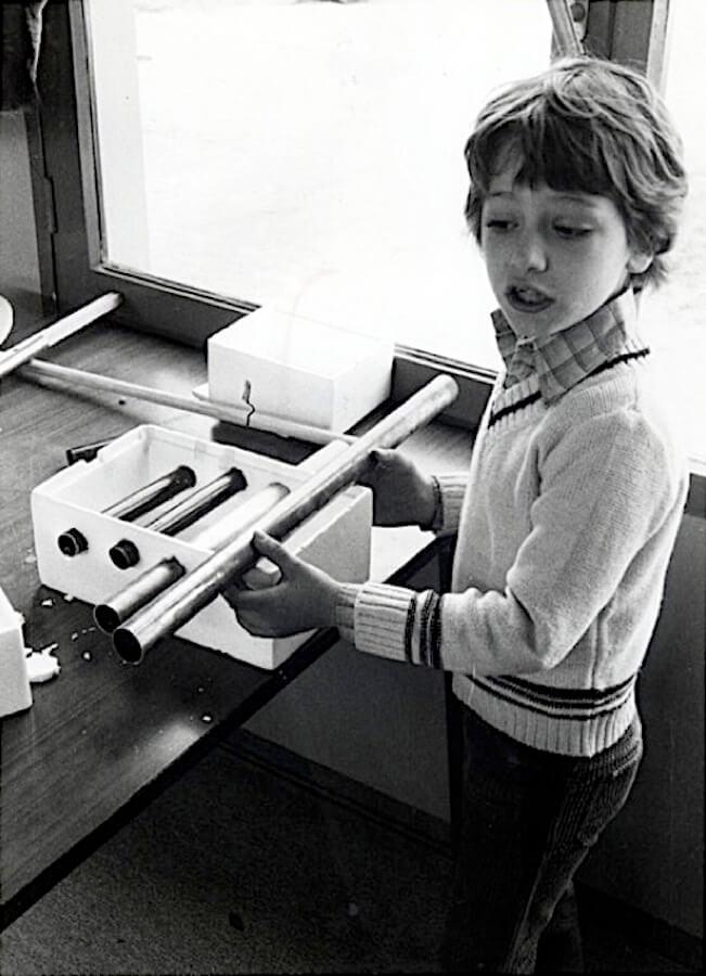 Photographie Noir et Blanc, un enfant assemble des tubes sur une boite en polystyrène expansé