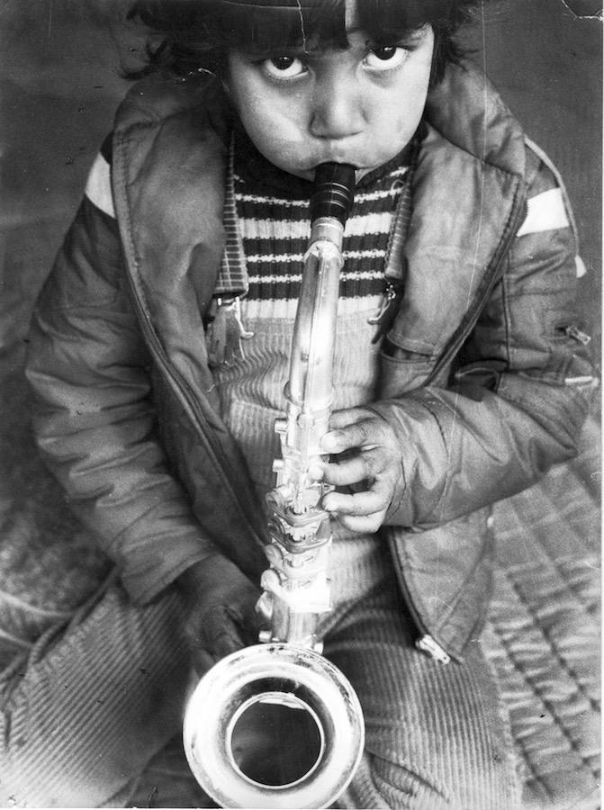 Photographie Noir et Blanc, un enfant regarde l'objectif en soufflant dans un petit saxophone