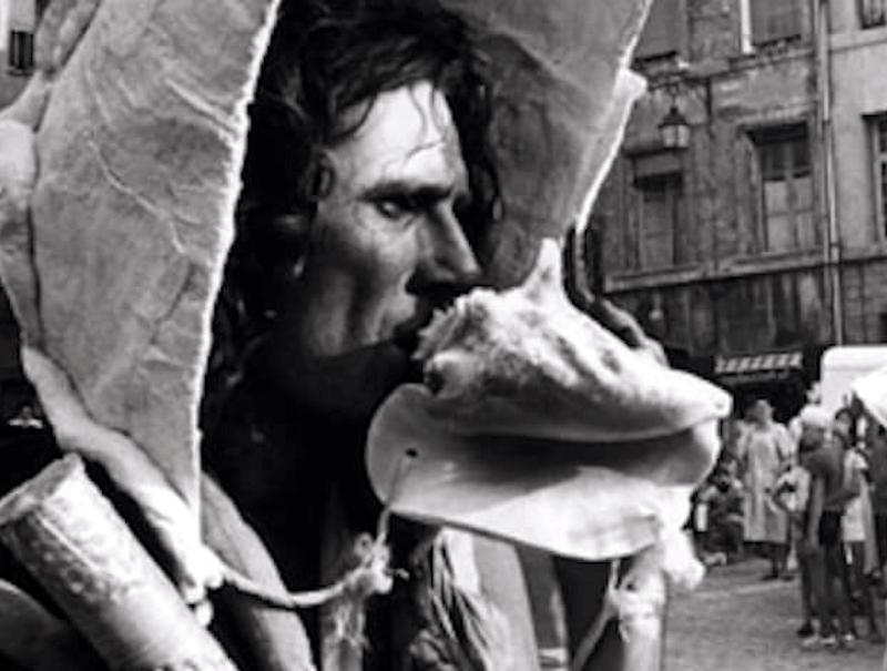 Photographie Noir et Blanc tête d'homme avec un casque coquillage géant soufflant dans une grosse conque
