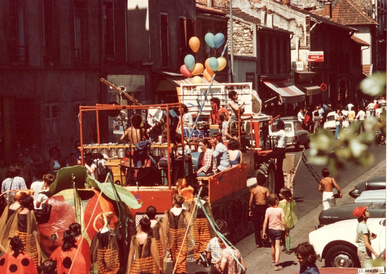 Photographie couleur : défilé carnaval avec enfants déguisés précédés par un camion-plateforme où jouent un orchestre de percussion avec une dizaine d'enfants et 4 adultes.